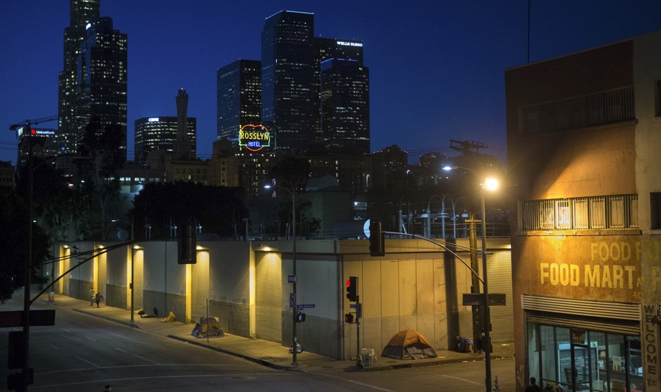Homeless people sleeping in tents under streetlamps with the LA skyline beyond.