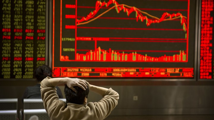 An investor holds his head in front of a red screen with fluctuating stock prices
