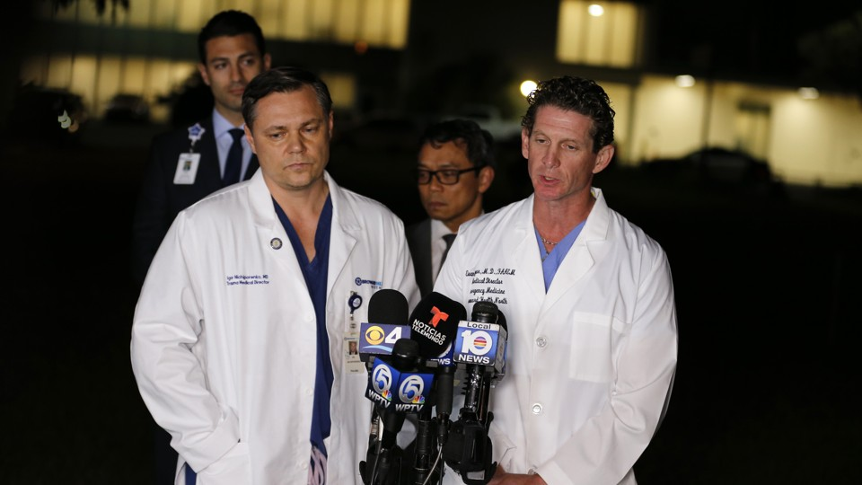 Two doctors in white coats stand in front of microphones