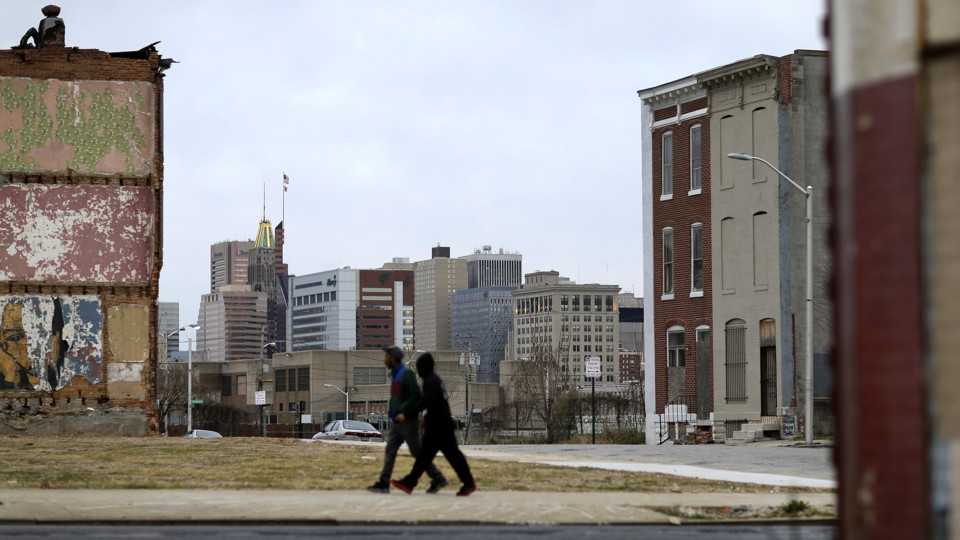 Two people walk past a vacant lot and boarded-up homes
