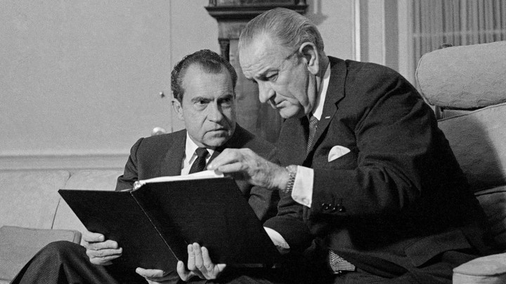 Lyndon B. Johnson and Richard Nixon speak in the Oval Office.