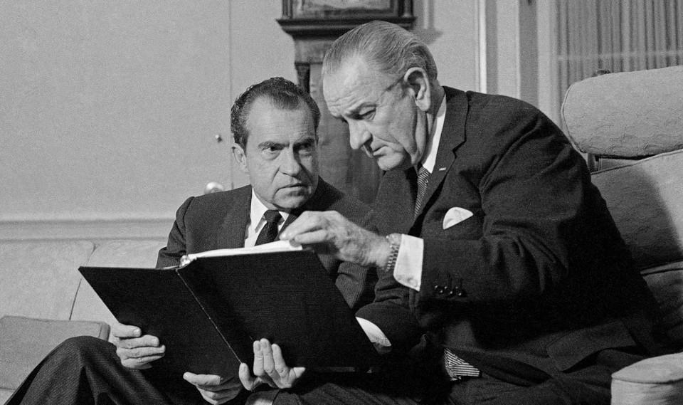 Lyndon B. Johnson and Richard Nixon speak in the Oval Office.