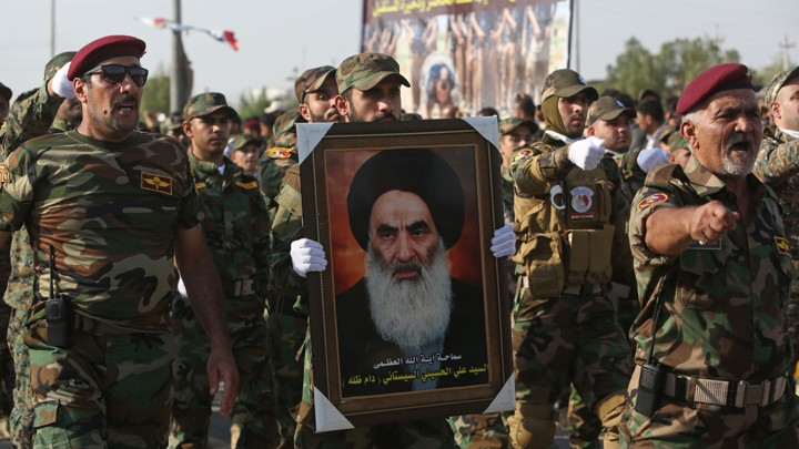 Members of the Abbas combat squad, a Shiite militia group, carry a picture of Grand Ayatollah Ali al-Sistani.