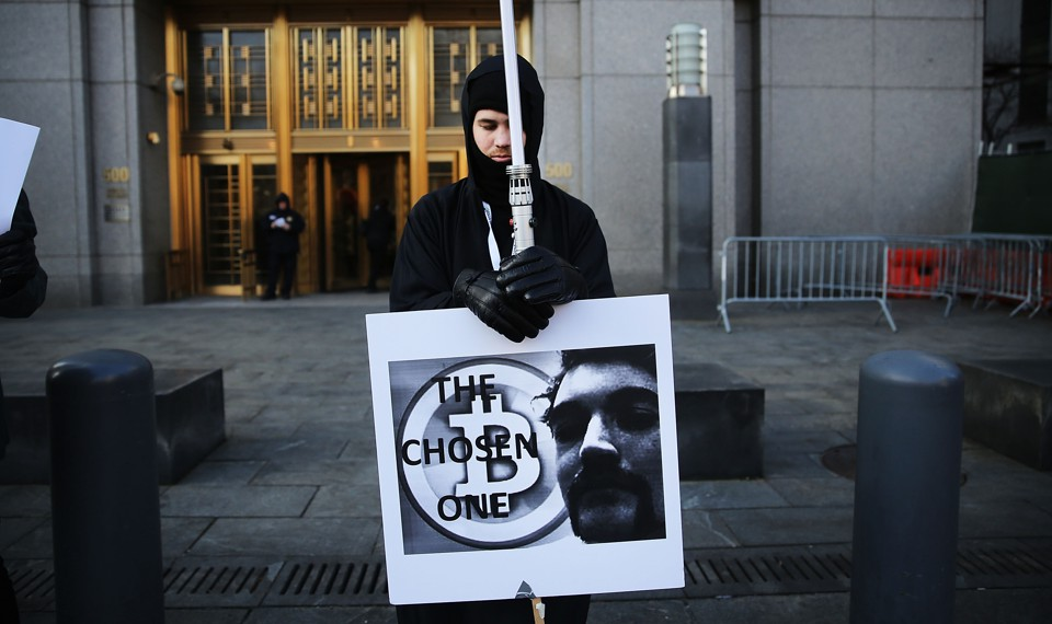 A man dressed in black holds a sign with a symbol for bitcoin