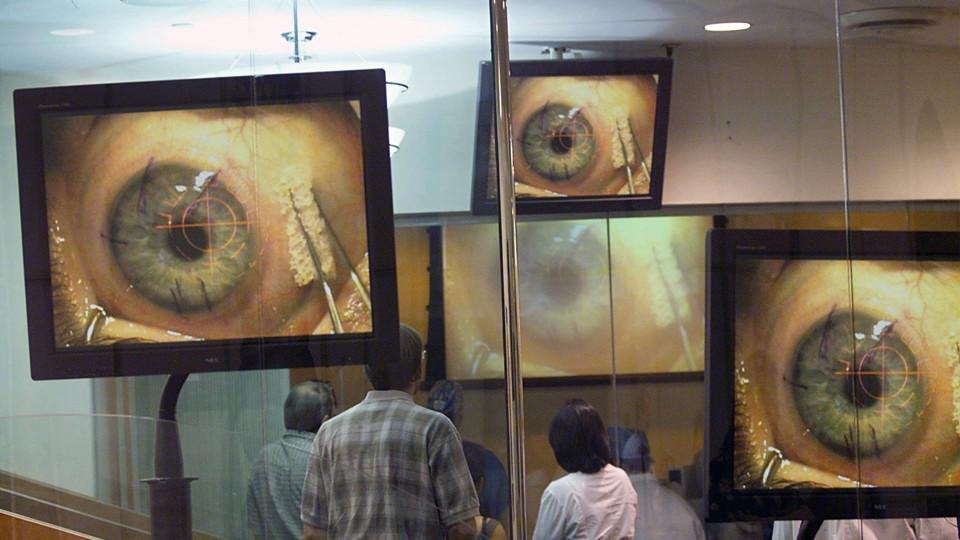 Closeups of an eye on several television monitors