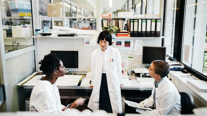 Three people in lab coats converse in a lab space with computers.