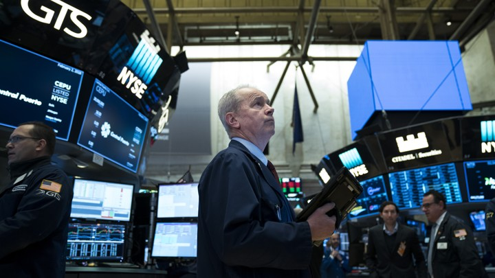 A trader looking up at screens on the stock exchange floor