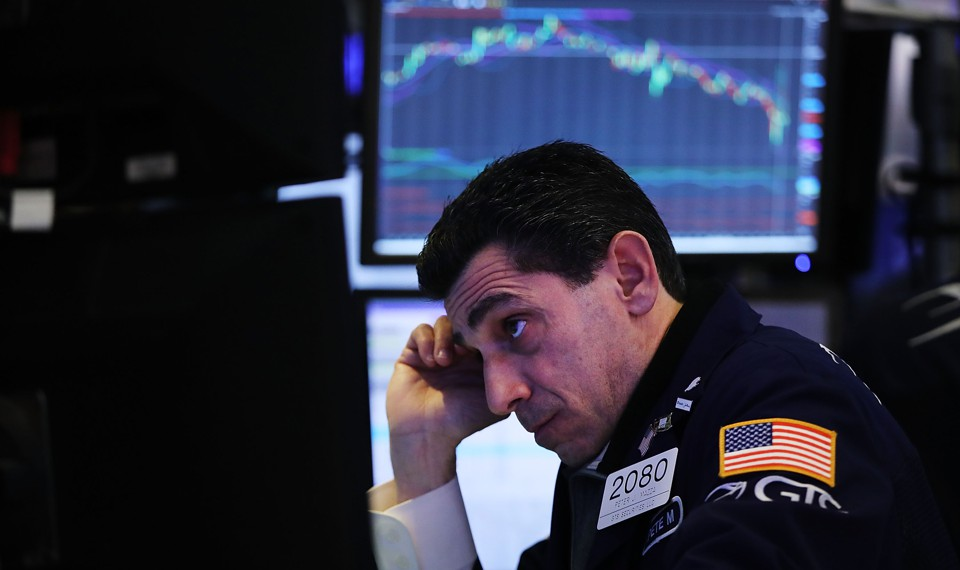 A stock trader looks at a computer screen