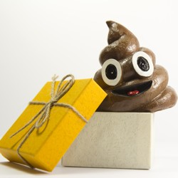 A smiling, cartoonish pile of poop next to a gift-wrapped box
