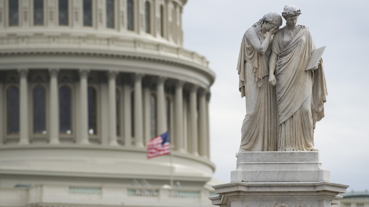 An American flag flies at half staff over the U.S. Capitol and behind the Peace Monument in Washington, D.C.