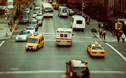 A city street with an ambulance, buses, cars, and taxis