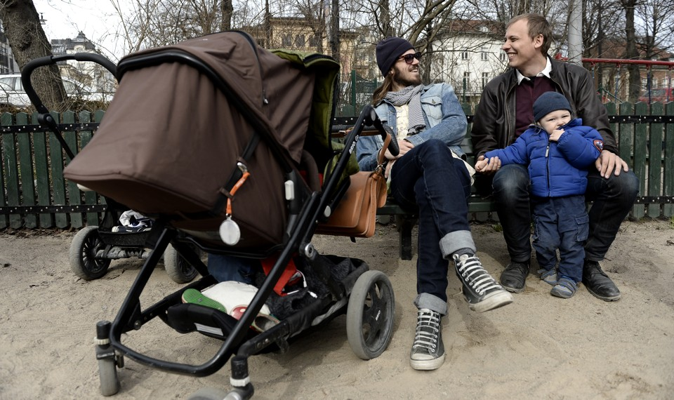 Anders Veide looks on as his friend Set Moklint plays with his child during paternity leave in Stockholm, Sweden.