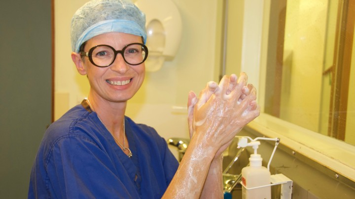 Liz O'Riordan in surgical scrubs, washing her hands