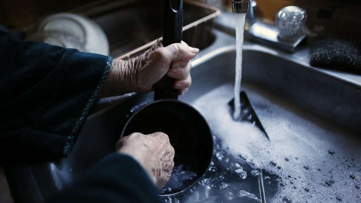 an elderly womans hands washing a pot in a sink