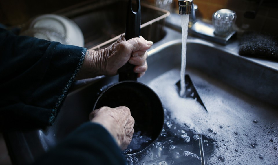 An elderly woman's hands washing a pot in a sink