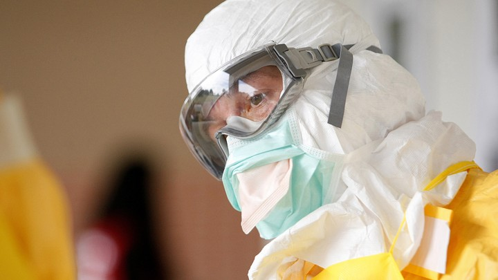 A person wearing a full protective suit, googles, and a surgical mask