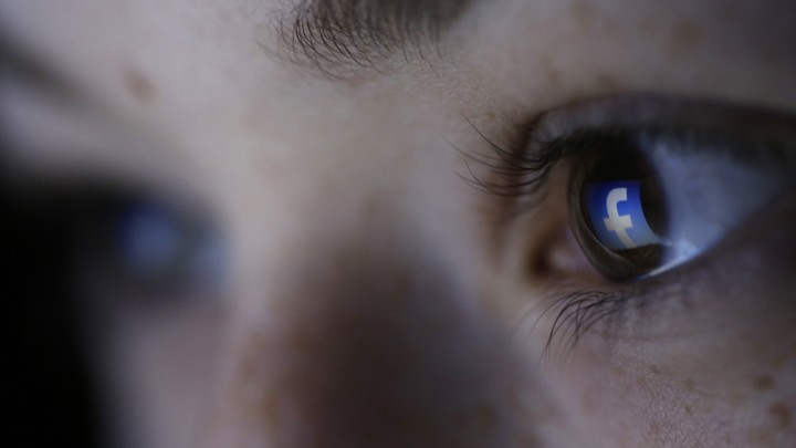 The Facebook logo reflected in a person's pupil