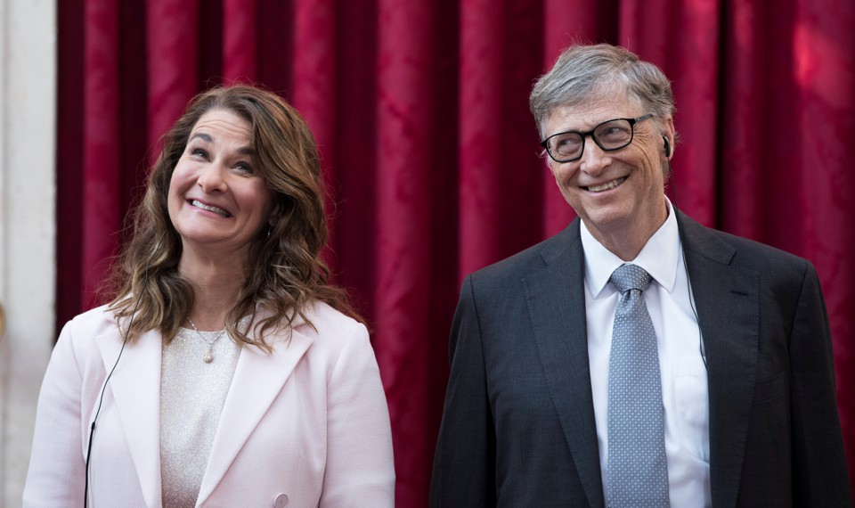 Bill and Melinda Gates smile broadly in front of a red curtain.