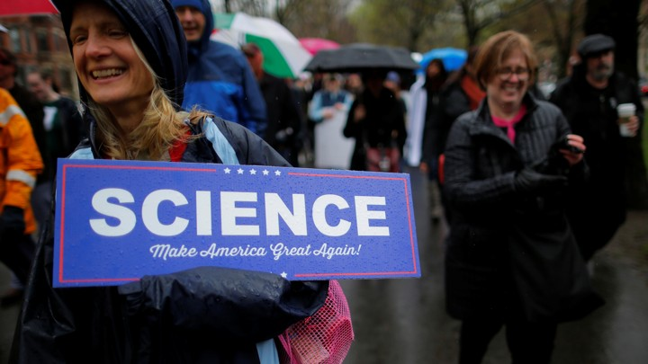 "A woman at a rally holds a sign that says ""Science: Make America Great Again!"""