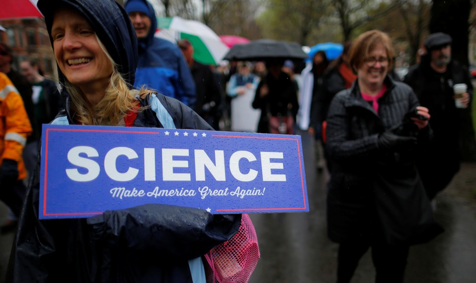 """A woman at a rally holds a sign that says """"Science: Make America Great Again!"""""""