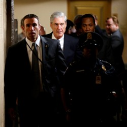 Special Counsel Robert Mueller and other officials walk down a hallway accompanied by a police officer.