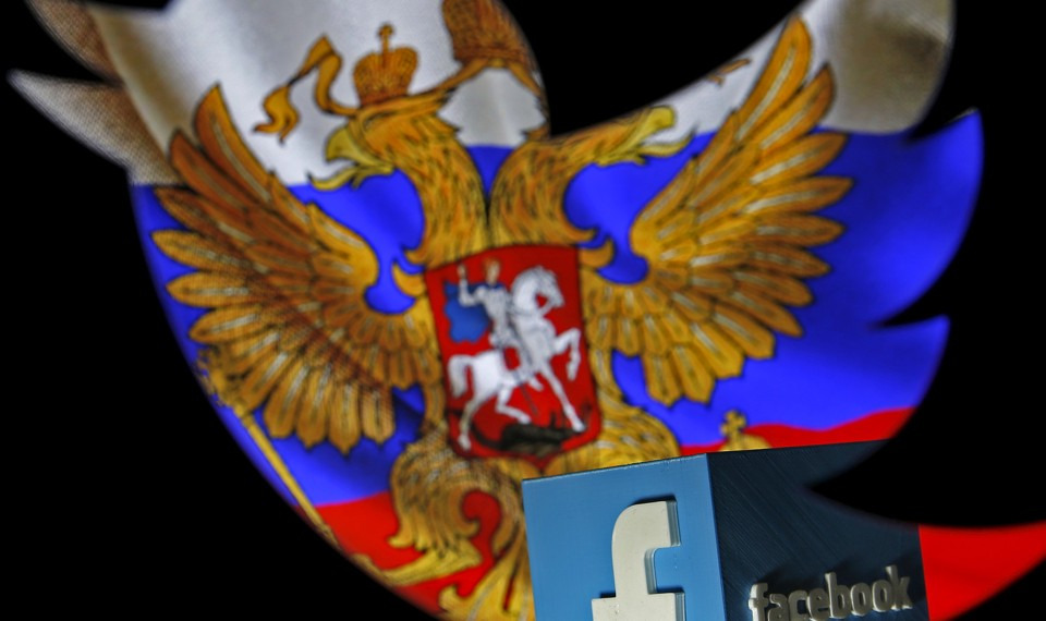 A Russian flag is seen next to the Facebook logo