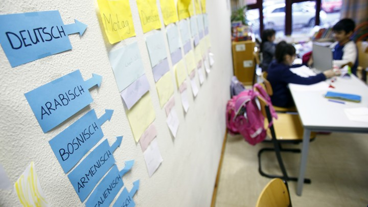 Students sit near a classroom wall with notes stuck to it naming languages and words in those languages.