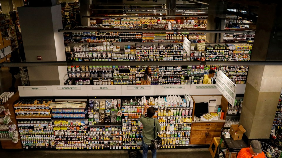 A customer in front of many stocked aisles at a Whole Foods