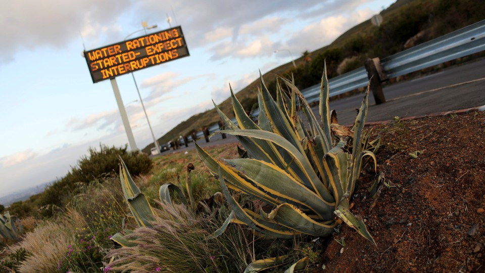 "A highway sign that reads, ""water rationing started—expect interruptions"""