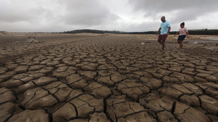 A family negotiates their way through caked mud around a dried up section of the Theewaterskloof dam.