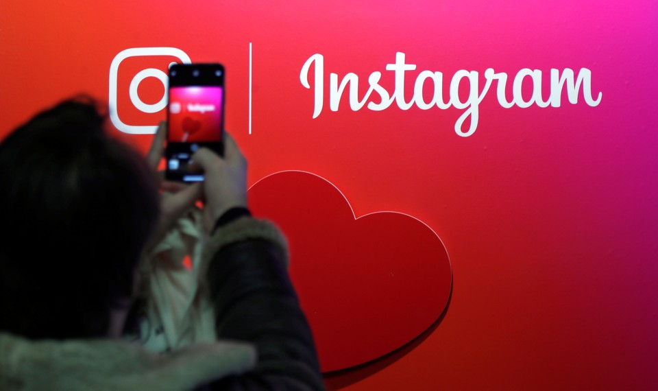 A person uses their cellphone to take a photo of the Instagram logo.