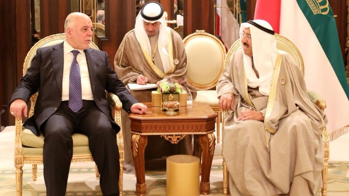 Iraq's prime minister, who is dressed in a suit, talks to the emir of Kuwait, who is dressed in traditional clothes.