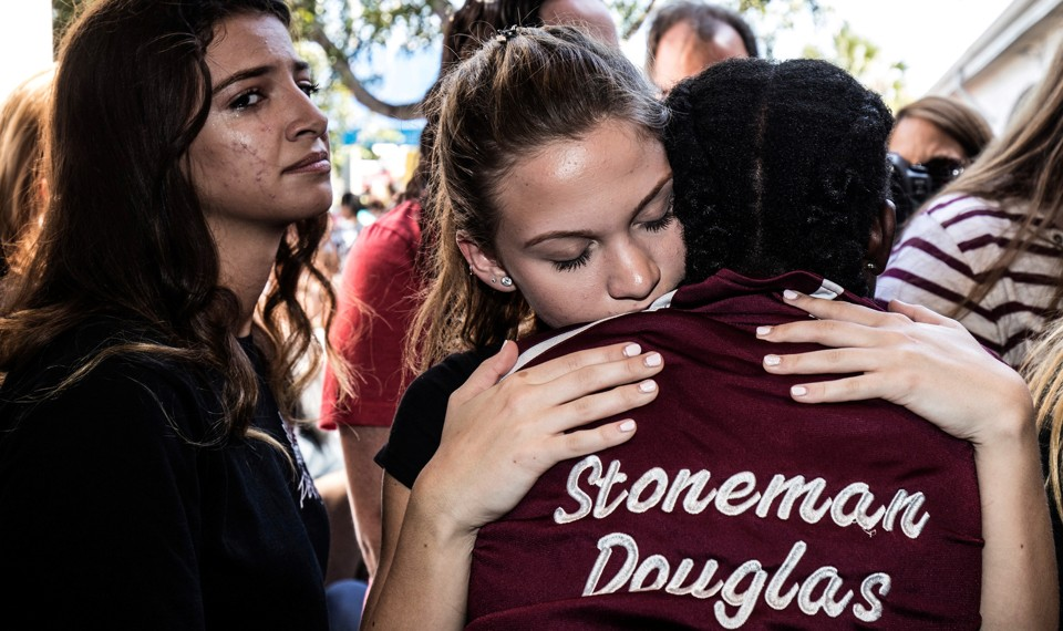 """Young people hug. One is wearing a jacket that says """"Stoneman Douglas"""" on the back."""