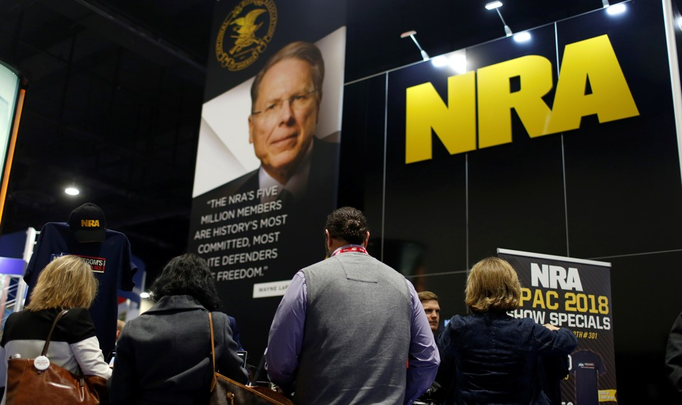 People in front of a booth with a picture of Wayne LaPierre and the NRA logo