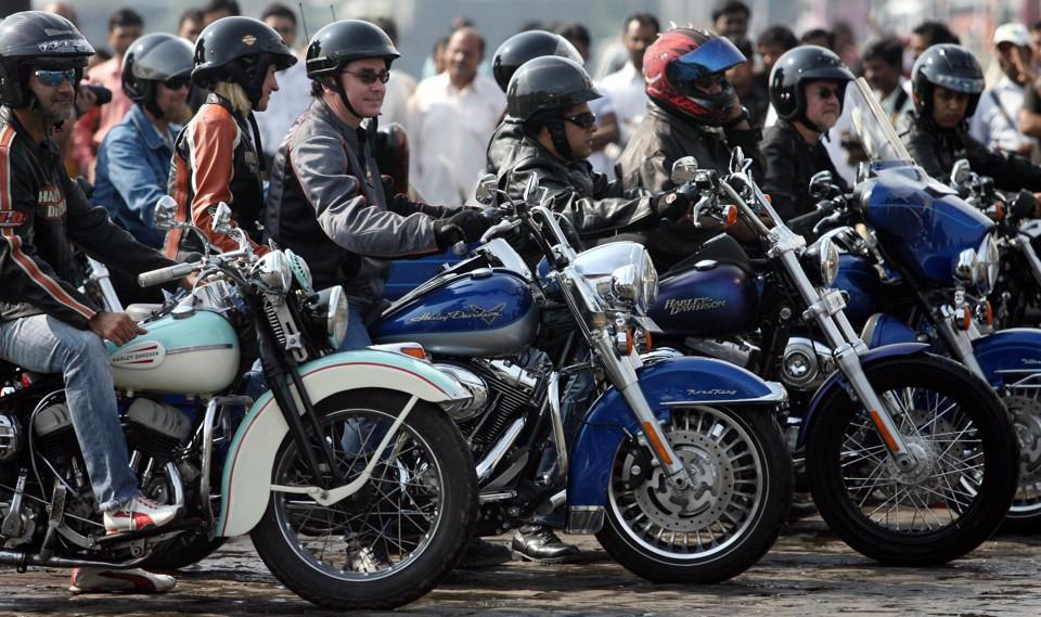 Helmeted riders sit on motorcycles
