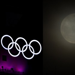 A Super Moon rises through the clouds past the Olympic Rings.