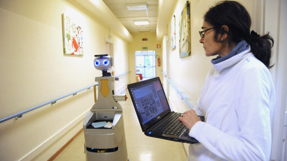 A human caregiver uses a laptop to operate a robot caregiver in the hallway of a nursing residence.