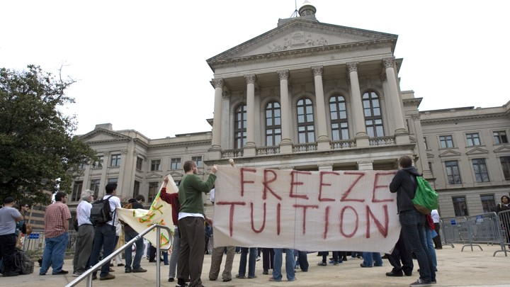 "Students and alumni hold a sign that reads ""Freeze Tuition."""
