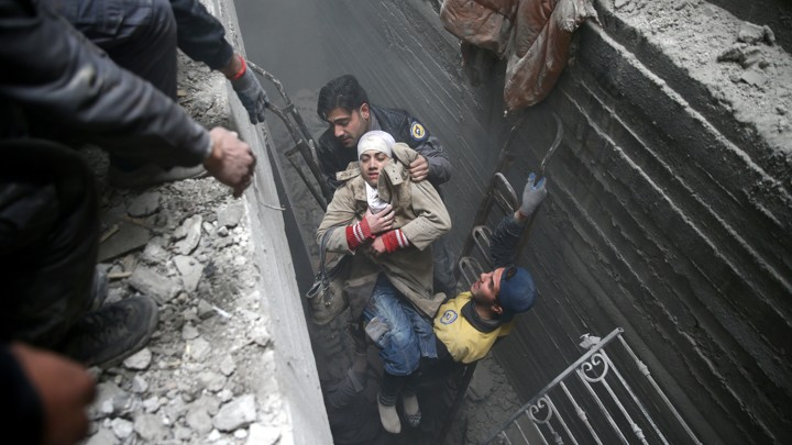 Syria Civil Defence members help an unconscious woman from a shelter in the besieged town of Douma, Eastern Ghouta, Damascus, on February 22, 2018.