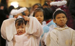 Children dressed as angels attend a Christmas Mass in a Catholic church in Beijing.