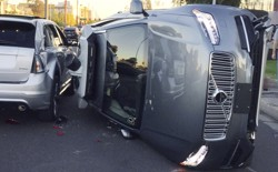 A flipped over grey self-driving SUV