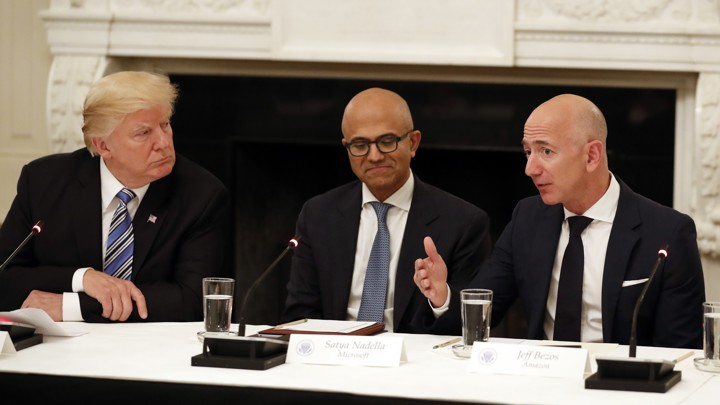 Donald Trump, Satya Nadella, and Jeff Bezos seated at a table