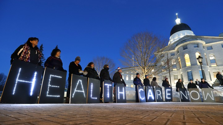 Holding signs, members of a pro-Medicaid group stage a rally outside a government building in Maine.