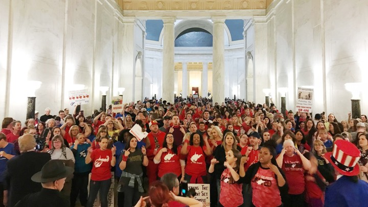 West Virginia teachers in red shirts cheer in the state Capitol after a deal was reached to end their strike.