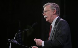 John Bolton speaks at a microphone.