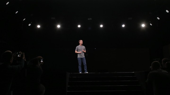 Mark Zuckerberg on a stage being photographed and lit by spotlights