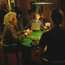 Stephen Hawking and actors dressed as Isaac Newton and Albert Einstein sit at a poker table surrounded by a film crew.