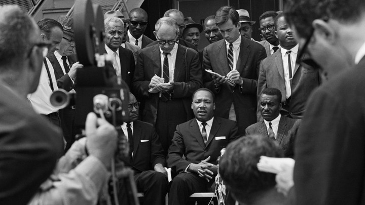 Martin Luther King Jr. speaks in front of news cameras and reporters with notepads, flanked by Fred Shuttlesworth and L.H. Pitts.