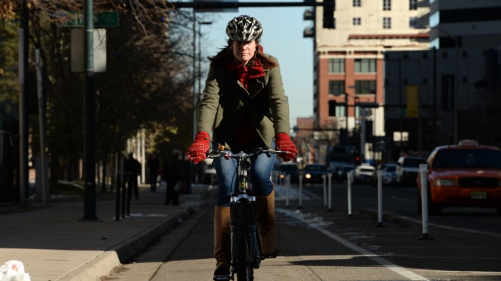 A woman rides a bicycle down a bike lane in Denver