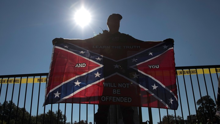 A man holding a Confederate flag